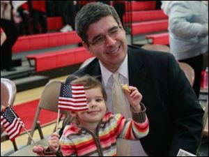 Sofia Ollervides, 3, left, celebrates with American flags as her father Francisco Jose Ollervides, of Caledonia, smiles after becoming a naturalized U.S. citizen.