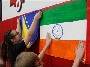 St. Kateri Catholic Academy sixth graders Katie Steck, 12, left, and Mason Huntermark, 12, put up flags they made at the start of the ceremony. The children made flags of the countries the new citizens had left. The flag at left is that of Bosnia-Herzegovina, and the one at right that of India.