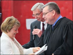 Mariana Steffan, originally of Russia, is welcomed as a U.S. citizen by U.S. District Court Judge James R. Knepp, right. Behind Knepp, and center, is James McGuire, an officer from the USCIS.