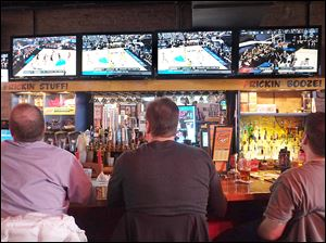 Walls of TV screens occupy patrons of Fricker's downtown who watched the first games of the NCAA basketball tournament. Businesses such as sports bars count on March Madness, which began Thursday, for a financial boost during the doldrums of late winter and early spring.