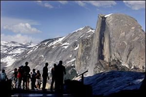 Visitors view Half Dome from Glacier Point at Yosemite National Park. Permits and lodging in the national parks go fast. People who leave planning to the last minute will find slim pickings.
