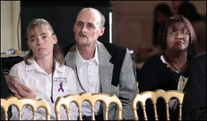 Kirk Smalley, center, and his wife Laura, left, of Perkins, Okla., and Sirdeaner Walker from Springfield, Mass., listen at the Conference on Bullying Prevention in this 2001 file photo in the East Room of the White House in Washington.