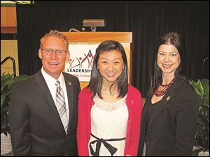 Bill Garbe, Connect for Leadership event chairman, left, with student speaker Jenny Kim, center, and Carrie Serber, board chairman.