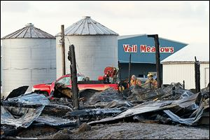Firefighters remain on the scene after an early morning barn fire at the Vail Meadows Equestrian Center on Cedar Point Road in Oregon on Thursday.