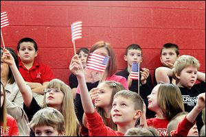 Jeremiah Duvall, center, holding up a U.S. flag, and other second graders wave Old Glory during the naturalization ceremony at Cardinal Stritch.