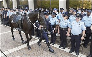 Sgt. Mike McGee of the Toledo Police Department Mounted Patrol and a Vail son-in-law, leads his horse, Harley, past fellow officers during a 2004 memorial service for officers who died in the line of duty. Harley, nearly 24, was one of the horses who died in the barn fire. The McGees acquired Harley in 2005.