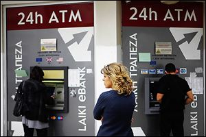 A woman waits to use an ATM machine in Nicosia, Cyprus, last week. Cypriots withdrew cash out of fear of a proposed tax on bank deposits.
