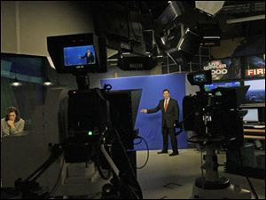 Co-anchor Kristian Brown, left, waits as chief meteorologist Jay Berschback, center, gives the weather report.