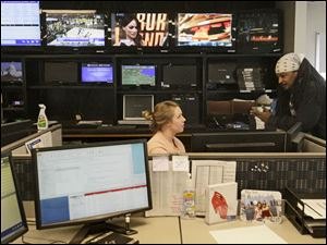 Special projects producer Shelly Gorringe, left, talks with photographer and editor Derrick Thurmond at her desk.