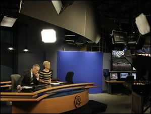 Co-anchors Lee Conklin, left, and Diane Larson wait to go live during a commercial break.