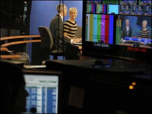 Co-anchors Lee Conklin, left, and Diane Larson talk during a broadcast.