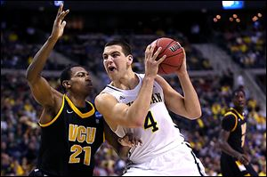 Michigan's Mitch McGary drives against Treveon Graham of Virginia Commonwealth. McGary controlled the inside, scoring 21 points to lead the Wolverines (28-7).