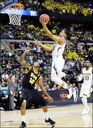Michigan's Trey Burke drives on Virginia Commonwealth's Darius Theus in the first half. Burke scored 18 points for the Wolverines.
