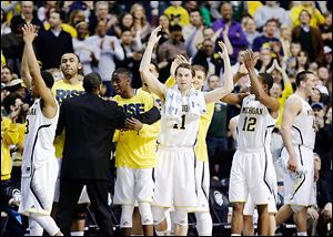 Michigan's Nik Stauskas (11) leads the cheers as the final seconds tick away in the Wolverines' victory over VCU. Michigan will now travel to Texas for a game at Dallas Cowboys stadium.