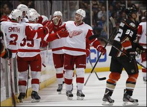 Detroit Red Wings' Justin Abdelkader, center, celebrates his hat trick during the second period Friday in Anaheim, Calif.