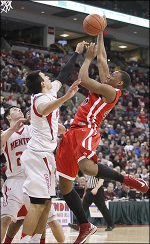 Rogers' Fadil Robinson goes up for a shot against Mentor's Brandon Fritts. Robinson finished with 10 points.