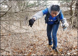 University of Toledo student Daija Thomas looks for trash at Ottawa Park during UT's annual Big Event.