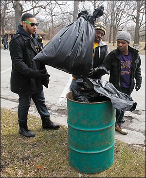 From left, University of Toledo students Jahziel Soriano, Eric Norvell, and Ibrahim Shafau dump collected trash into a can at Ottawa Park.