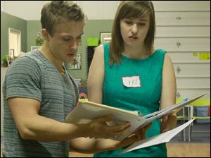 Director Clark Ausloos, left, gives another song to Perrysburg High senior Morgan Brunsman during her audition.