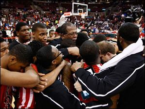 Rogers head coach Earl Morris consoles his team after losing to Mentor.