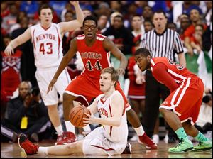 Rogers' DeVonte Pratt (32) and Alejandro Williams (44)chase a loose ball against Mentor's Michael Gallagher (31).
