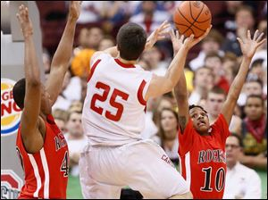 Rogers' Fadil Robinson (40) and Kevon Davis (10) defend against Mentor's Caleb Potter (25).