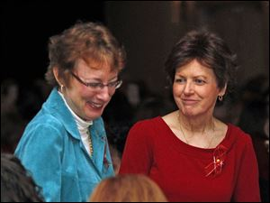 Karen Zolg, left, and Deb Fenn are among women in the audience being acknowledged for being cancer survivors during the Victory Center â'œRadiant in Red'€ Fashion Show.