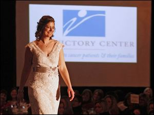 Cancer survivor Mary Pollock strolls down the runway in an elegant white lace gown.