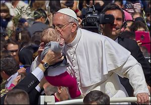 Pope Francis kisses a baby after celebrating his first Palm Sunday Mass in St. Peter's Square at the Vatican on Sunday.