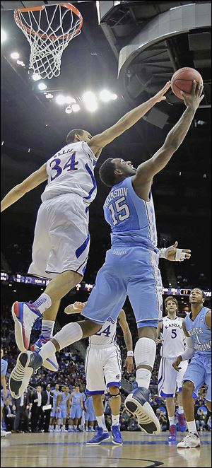 North Carolina's P.J. Hairston, right, shoots under pressure from Kansas' Perry Ellis during the first half. The top-seeded Jayhawks over came a sluggish start to pick up the 70-58 victory.