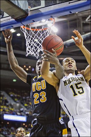 Michigan forward Jon Horford, right, tangles with VCU's Jarred Guest in Saturday's game. The Wolverines are 6-1 on neutral courts this season as they head to Dallas to play in Cowboys Stadium.