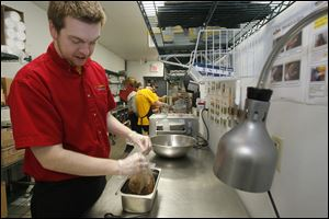 Assistant manager Jacob Hoover, 24, of Bowling Green, gets ready to shred pork, one of the options at the restaurant.