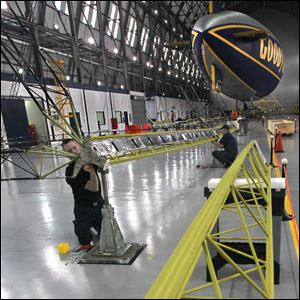 Goodyear airship mechanic Tom Bradley, left and Marcus Draeger, an airship mechanic with the German Zeppelin Corporation, work on a section of the interior frame as construction of the first of the Goodyear Rubber & Tire Company's new fleet of airships, the Goodyear NT, begins at the Wingfoot Lake hangar.