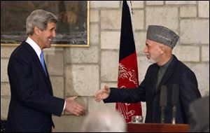 Secretary of State John Kerry reaches to shakes hands with Afghan President Hamid Karzai at the end of their joint news conference at the Presidential Palace in Kabul.