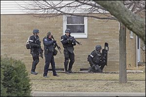 Members of a special response team made up of officers from Maumee, Sylvania, and Sylvania Township get into position Sunday near 1145 Kirk St. in Maumee.