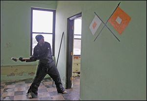Greenspace worker Nick Gillespie removes door frames in preparation to demolish the Michigan National Guard armory in Monroe.