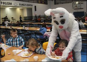 Robbie Moore, left, watches the Easter Bunny take Abby Moore's plate during the pancake breakfast.