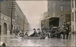 Floods that swept through Ohio in March, 1913, caused millions of dollars in damage and took hundreds of lives. While Toledo escaped major damage, boats, such as the one above on Water Street looking south from near Adams Street, were used for what rescue work was needed. This photo first ran in The Blade on March 26. 1913.