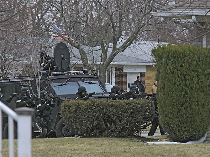 CTY_Standoff24p SWAT A Special Response Team prepares to enter a home on Kirk Street in Maumee Sunday after a shooting suspect barricaded himself inside. Police entered the home after a five-hour standoff.