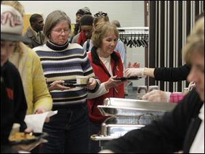 Owens Community College secretary Linda Flowers, enter, smiled as she received food in a buffet line.