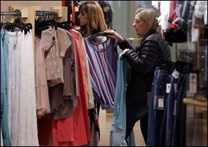 In this March 5, 2013 photo, shoppers look at clothing on sale at the Footloose store in Mt. Lebanon, Pa. The Conference Board, a New York-based private research group, said its reading of consumer confidence fell in March after rebounding last month. The index gauges how Americans are feeling about their jobs, incomes and other bread-and-butter issues.