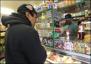 A store employee, right, at Apple Deli Grocery helps a customer, Tuesday, March 26, 2013, in Passaic, N.J. The employee would only identify himself as the son of Pedro Quezada, the 44-year-old man who won the $338 million Powerball jackpot after purchasing the winning ticket at Eagle Liquors store in Passaic.