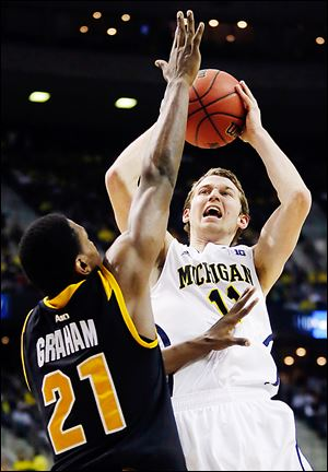 Michigan guard Nik Stauskas shoots over VCU's Treveon Graham during the Wolverines' 78-53 win Sunday. They play top-seeded Kansas in the Sweet 16 on Friday night.