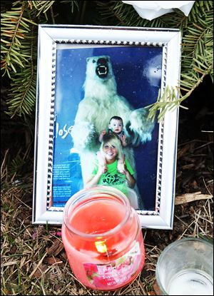 A photo of Kaitlin Gerber, with her nephew Nico Gerber, taken at the Toledo Zoo sits among items that have become part of a makeshift memorial at the Southland Shopping Center.
