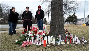Chris Murray, from left, Sarah Sutphin, and Russell Castillo, pause at a makeshift memorial for Kaitlin Gerber, at the Southland shopping center at Glendale Avenue and Byrne Road on Tuesday, March 26, 2013.  They are friends of Ms. Gerber, who was shot to death at the site by former boyfriend Jashua Perz on Sunday.