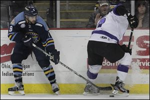 Toledo's Aaron Bogosian (9) pulls the puck away from Reading's Nikita Kashirsky earlier this month.