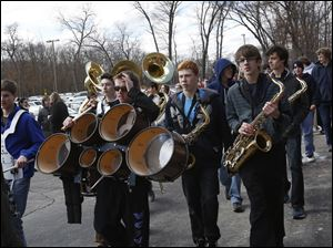 Adam Lucas, 17, center, hoists up his drums as he and fellow band members walk trough the parking lot.