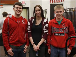 Chad Selnek, 17, left, Lizzi Sares, 18, center, and Phil Cook,18, stand for a photo during marching band class.