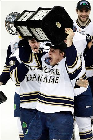 Notre Dame's Anders Lee lifts the CCHA hockey championship trophy in this file photo.