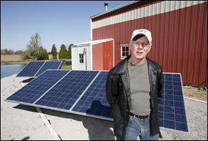 Dan Kronfield with his solar power generating equipment at his home on Five Points Road.